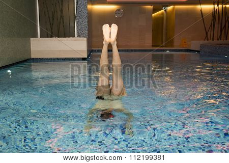 Man standing on hands in swimming pool