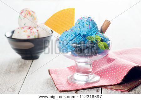 Blue ice cream and vanilla icecream on white rustic wooden background.