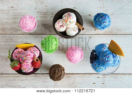 Top view strawberry, blueberry and vanilla ice cream in bowl on white rustic wooden background.