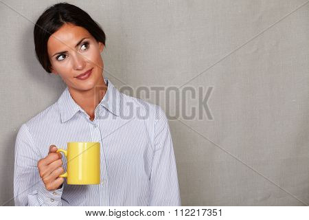 Well-dressed Lady Standing And Holding Yellow Mug