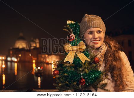Happy Woman With Christmas Tree Standing On A Bridge In Venice