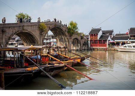 Wooden Chinese style boats parked next to a Venetian style bridge
