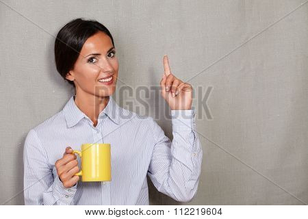 Smiling Female With Hot Drink Pointing Up