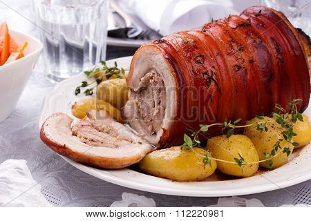Roasted Pork with potato and greenery.