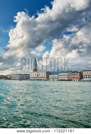 View from a boat of the Doges Palace and Campanile, Venice Italy with dramatic white clouds towering above in a travel and tourism concept