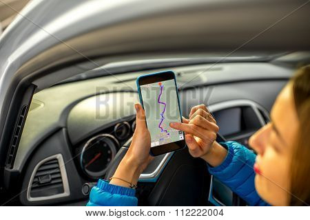 Female driver using smartphone in the car