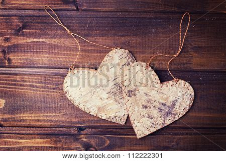 Two Decorative  Hearts On Dark   Painted Wooden Background.