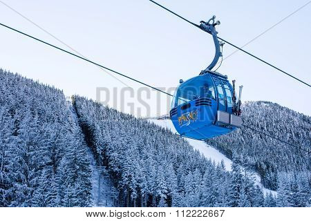 Close up Bansko cable car cabin, Bulgaria and snow covered pine trees