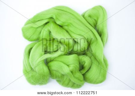 Lawn   green piece of Australian sheep wool Merino breed close-up on a white background.