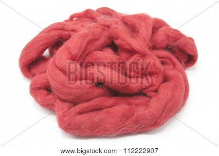 Cerise red piece of Australian sheep wool Merinos breed close-up on a white background.