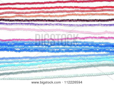 Background of threads with blue, pink, white and silver beads on white