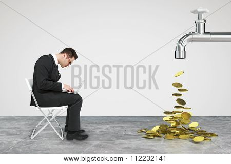 Working Businessman With Laptop And Faucet From Which The Money Flow