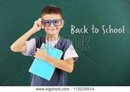 Beautiful little boy with book near blackboard