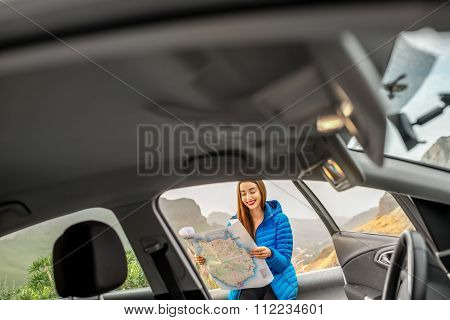 Female traveler with toursit map near the car