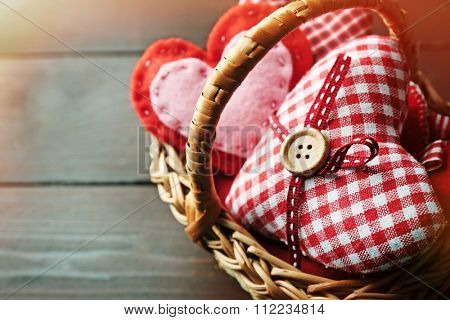 St Valentine's decor in basket on wooden background