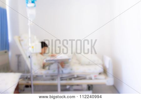 Blurred Image Of Patient With Drip In Hospital For Background Usage.