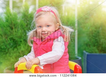 Portrait of cute little blond girl having fun on playground in warm sunny day, adorable kid playing outdoors, happy carefree childhood