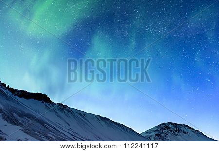 Amazing view on the Northern light and high mountains landscape covered with snow, forces of nature, Aurora Borealis, Iceland