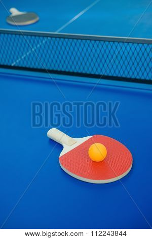 Pingpong Racket And Ball And Net On A Blue Pingpong Table Vertical