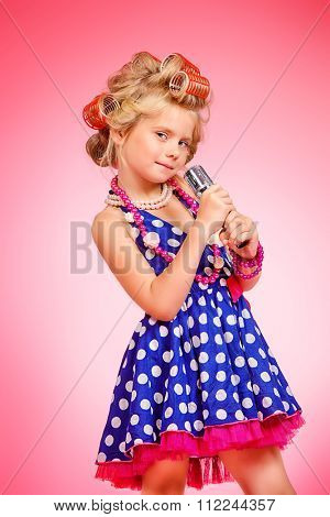 Beautiful little girl in her mother's hair curlers and polka-dot dress. Kid's fashion, cosmetics. Pin-up style.