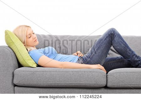 Young blond woman sleeping on a gray couch isolated on white background
