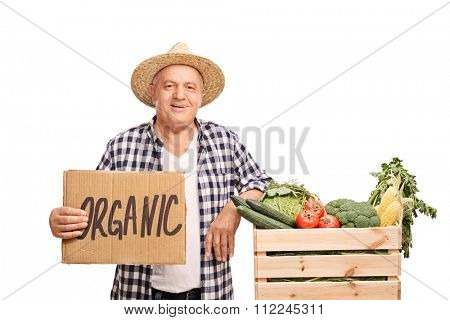 Mature farmer leaning on a wooden crate full of fresh vegetables and holding a cardboard sign that says organic isolated on white background