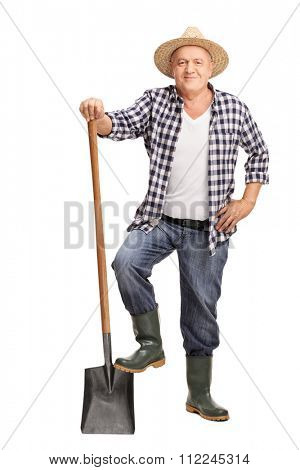 Full length portrait of a mature farmer posing with a shovel isolated on white background