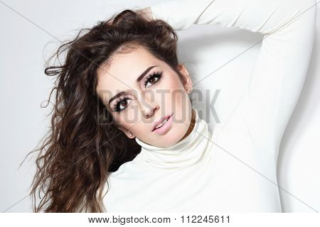 Young beautiful sexy brunette with long curly hair and false eyelashes