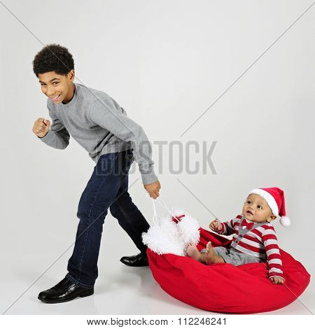 An elementary boy giving his baby brother a ride on Santa's sack.  On a gray background.