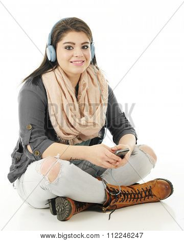 A pretty teen girl sitting cross-legged on the floor happily listening to her cell phone with headphones.  On a white background.