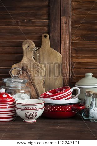 Rustic Kitchen Still Life. Olive Cutting Board,  Jar Of Flour,  Bowls, Pan, Enamelled  Jar,  Gravy B