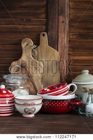 Rustic Kitchen Still Life. Olive Cutting Board,  Jar Of Flour,  Bowls, Pan, Enamelled  Jar,  Gravy B