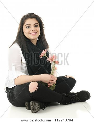 A beautiful teen girl happily holding a small bouquet of pink flowers as she sits cross-legged on the floor in a black and white outfit.  On a white background.