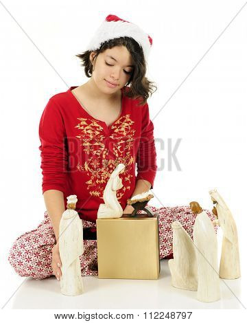 A young Hispanic teen arranging the Nativity characters while wearing her pajamas and a Santa hat.  On a white background.