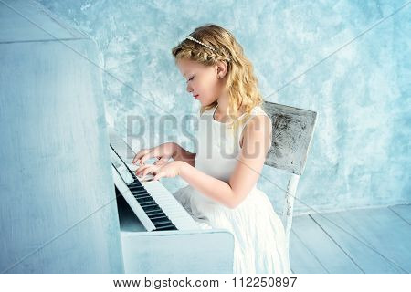 Beautiful eight year old girl in white dress playing the piano. Music and art concept. Vintage style.