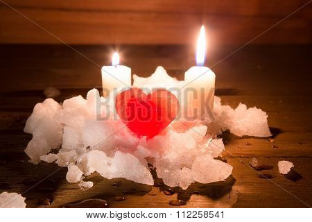 Red Ice Heart On A Snow Small Group On Wooden Boards And Two Burning Candles On A Background