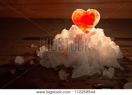 The Red Ice Heart On A Snow Small Group Lit With The Candle Burning Behind On A Wooden Surface