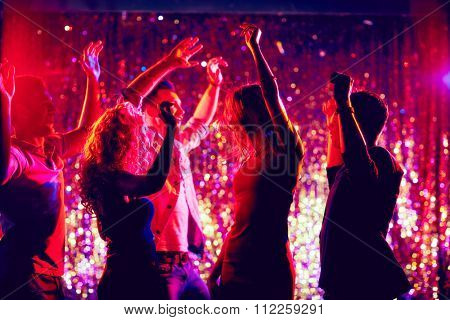 Group of young people dancing at party