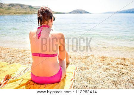 Beutiful Woman Sitting Sunbathing On The Beach With Legs In The Sea.