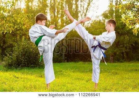 boys in white kimono during training karate exercises at summer outdoors