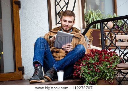 Smiling bearded young man in coat and jeans sitting on porch near entrance using tablet