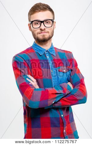 Handsome confident young bearded male in plaid shirt and glasses with folded hands