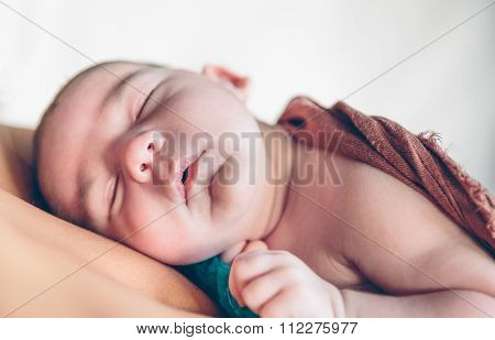 Newborn baby sleeping peacefully over the mother chest