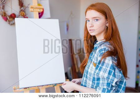 Portrait of beautiful pensive young woman painter in checkered shirt standing near blank easel in art classroom