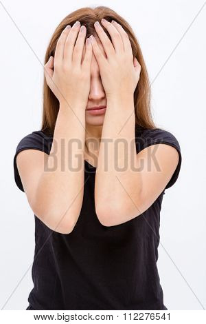 Stressed desperate young woman covered eyes by hands over white background