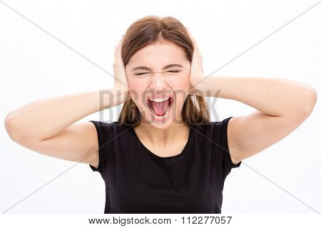 Angry irritated young woman with closed eyes covered ears by hands and shouting over white background