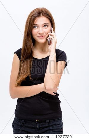 Beautiful joyful young woman talking on mobile phone over white background