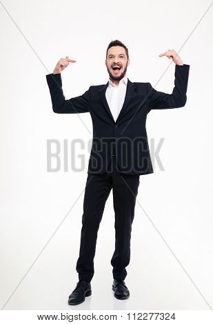 Handsome cheerful young businessman in black suit laughing and pointing on himself with both hands over white background