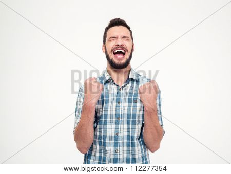 Excited elated happy bearded young male in checkered shirt celebrating success over white background