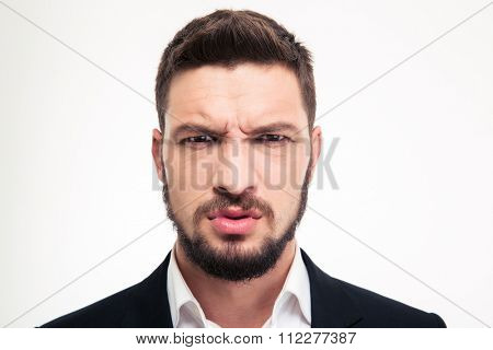 Close up of angry irritated bearded young business man in black suit and white shirt looking camera over white background